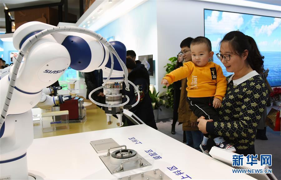 12月31日,别名儿童在家长的陪伴下不雅旁观展出的机器人。新华社记者 潘旭