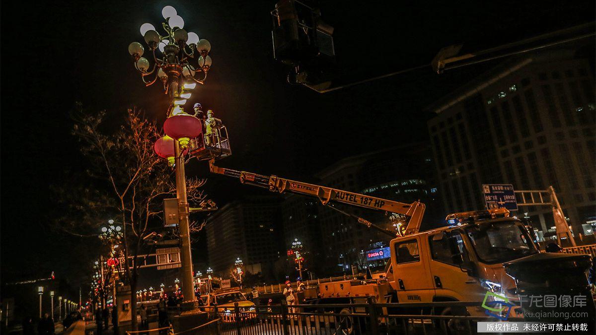 1月22日清早,国网北京电力城市照明管理中央的施工人员在长安街华灯上装配大红灯笼(图片来源:tuku.qianlong.com)。千龙网记者 陈健男摄