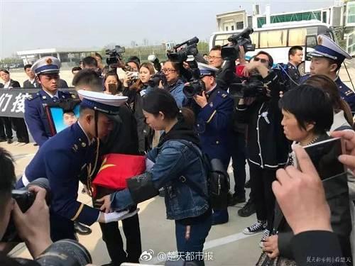 家乡的群众自发聚集在道路两旁,打起横幅、手捧鲜花,送英雄最后一程。