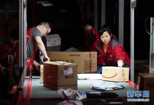 工人在位于西安的京东智能物流中心细分区龙门架下整理包裹(6月3日摄)。龙门架扫描后,包裹的出库物流信息将自动更新。新华社记者 邵瑞 摄