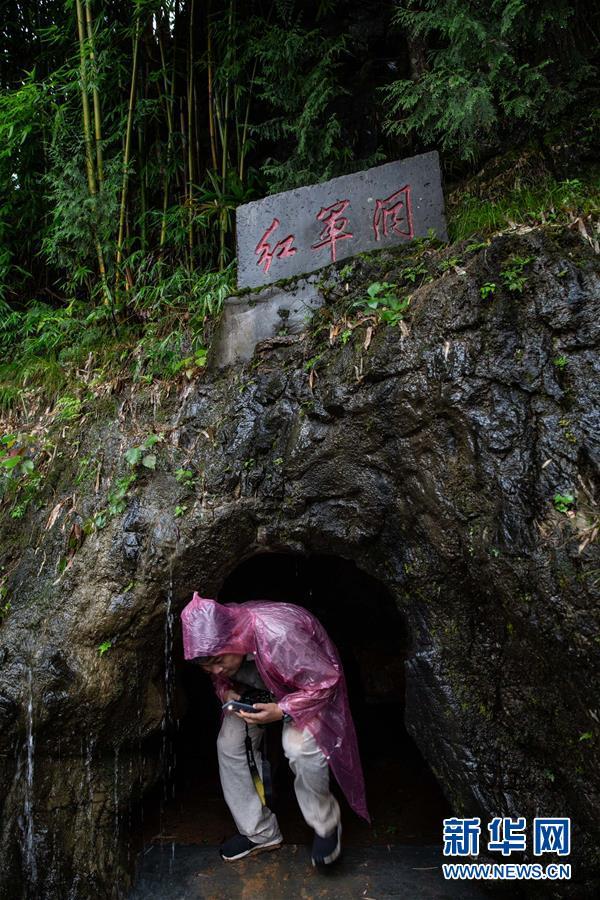 7月18日,在重庆秀山县雅江镇江西村的红军洞,一名记者弯着腰进行体验式采访。 新华社记者 吴壮