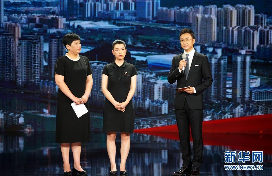 主持人(右)在仪式上向杨春的家人了解杨春的事迹(8月26日摄)。新华社记者 潘旭