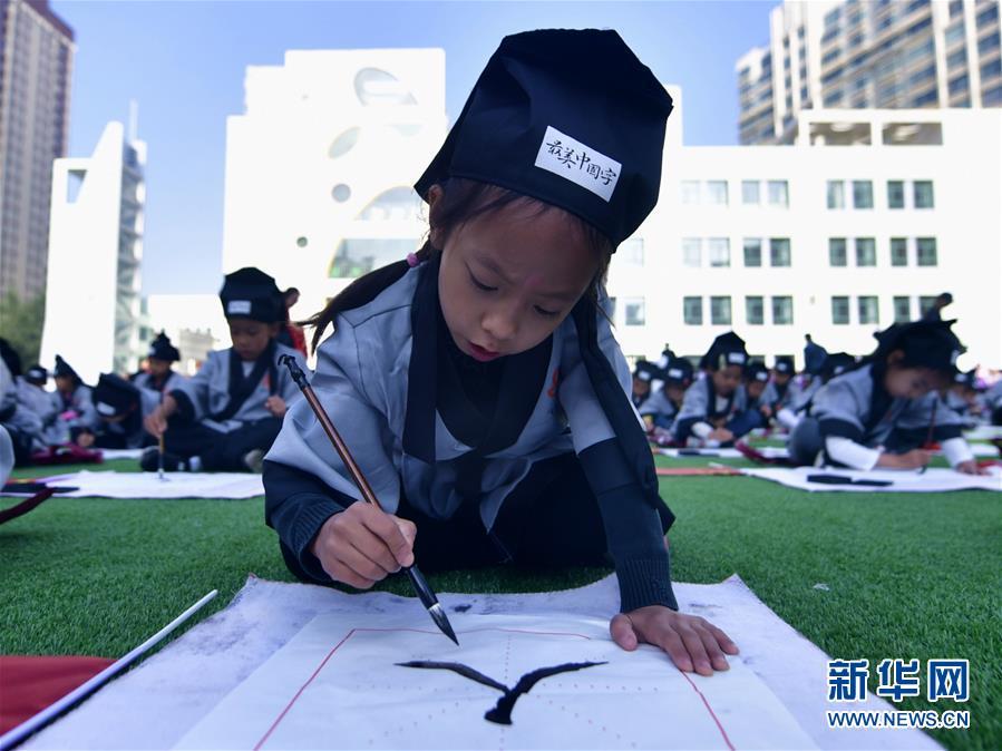 """9月1日,青海省西宁市文汇小学一年级的学生在""""开笔礼""""仪式上书写""""人""""字。 新华社记者 张龙"""