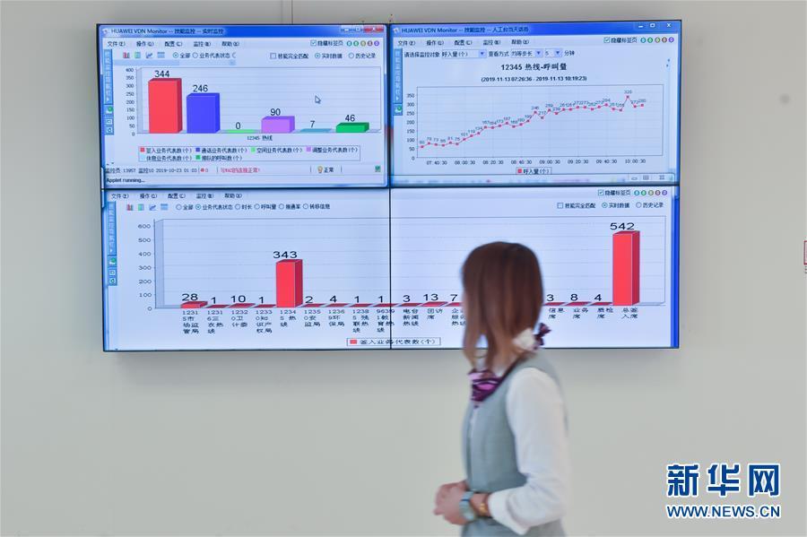 11月13日,在位于北京亦庄的12345市民热线话务大厅,一名工作人员从实时监控显示屏前走过。 新华社发(彭子洋摄)