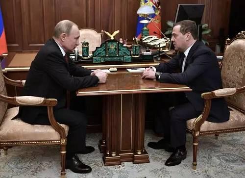 罗斯总统普京(左)在莫斯科与总理梅德韦杰夫交谈。(图源:新华社)