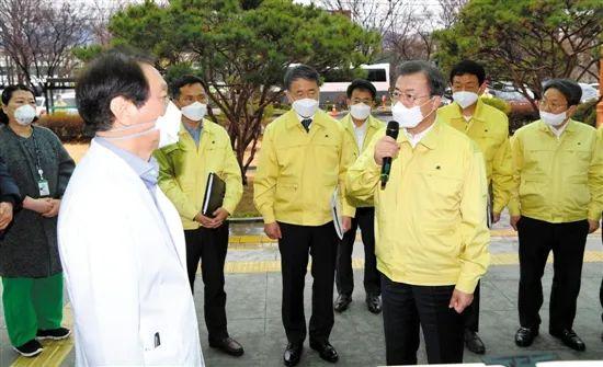 25日,韩国大邱,总统文在寅(前右)与当地医务人员交流。来源:新华社