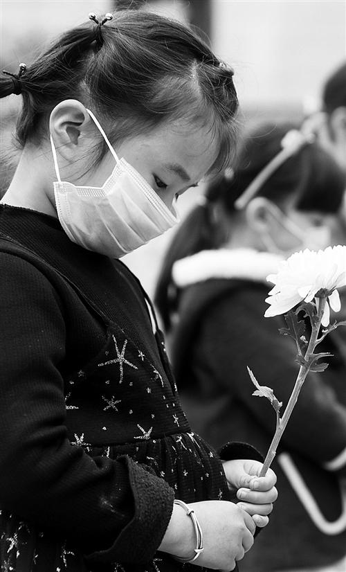 4月4日,四川省华蓥市华蓥山广场,一位小朋友手捧鲜花默哀。邱海鹰摄(中经视觉)