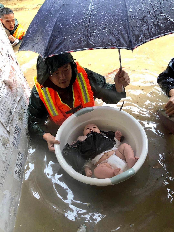 宜昌暴雨多人被困,消防队员用塑料盆安全转移婴儿
